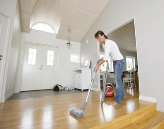 This is a picture of a woman vacuuming the floor.